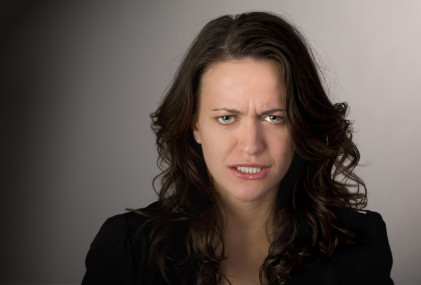 Emotional portrait of a frustrated woman against dark background